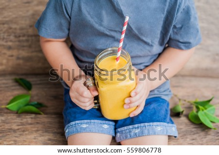 Boy drinking juicy smoothie from mango in glass mason jar with striped red straw on old wooden backg Stock photo © galitskaya