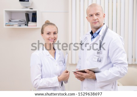Happy young successful clinician and her bald serious colleague in whitecoats Stock photo © pressmaster