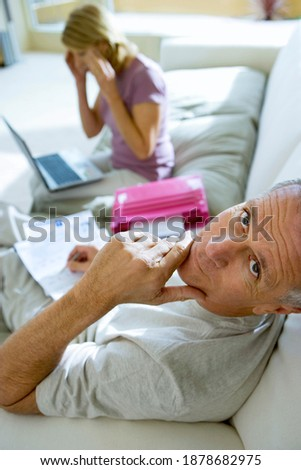 side view of active senior man smiling and using mobile phone in living room at home stock photo © wavebreak_media