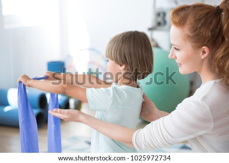physiotherapist helping the child exercising with elastic band stock photo © andreypopov