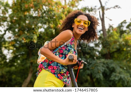 Pretty young woman riding an electric scooter in the street Stock photo © boggy
