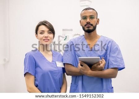 Successful young intercultural clinicians or interns in uniform looking at you Stock photo © pressmaster