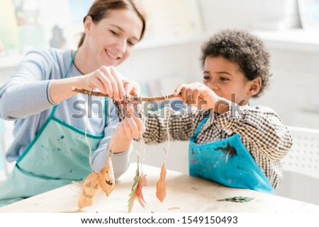 Cute schoolboy cutting one of threads with halloween decorations held by teacher Stock photo © pressmaster
