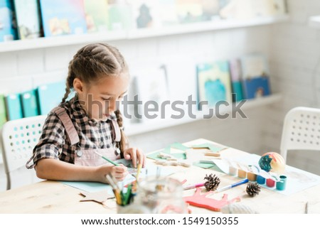 Cute casual schoolgirl with paintbrush drawing Christmas picture by desk Stock photo © pressmaster