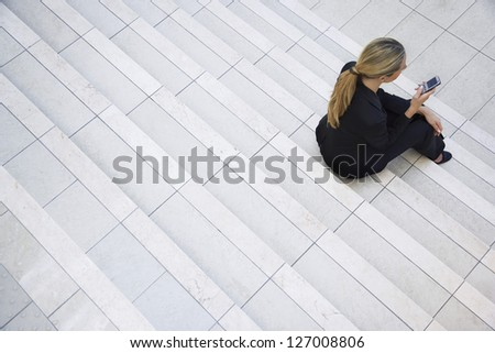 high view of caucasian female executive using mobile phone while moving down on escalator in modern stock photo © wavebreak_media