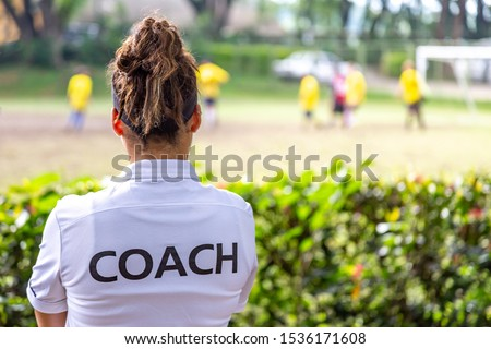 Female in sports uniform exercising on football field on background of players Stock photo © pressmaster
