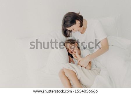 Top view of happy funny girl in pyjamas and her caring mom pose on bed, play together in bed, enjoy  Stock photo © vkstudio