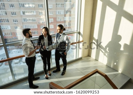 Group of three young contemporary analysts in formalwear discussing online data Stock photo © pressmaster