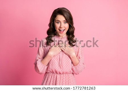 Pleased millennial girl with curly hair, wears pink dress, optical glasses, focused aside with smile Stock photo © vkstudio