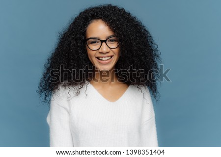 Headshot of lovely curly woman being in good mood, smiles broadly, expresses nice feelings, wears tr Stock photo © vkstudio