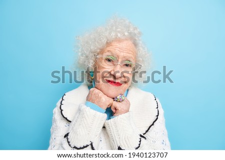 Portrait of delighted pleasant looking curly female keeps arms folded on chest, has confident facial Stock photo © vkstudio