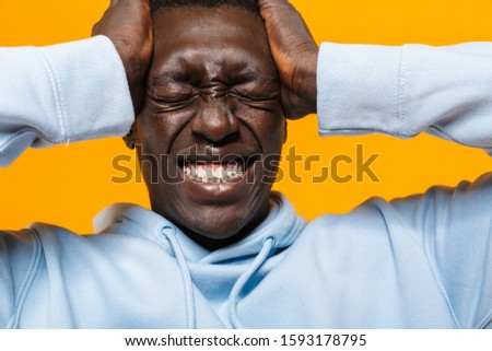 Image of tense african american guy suffering and grabbing his h Stock photo © deandrobot