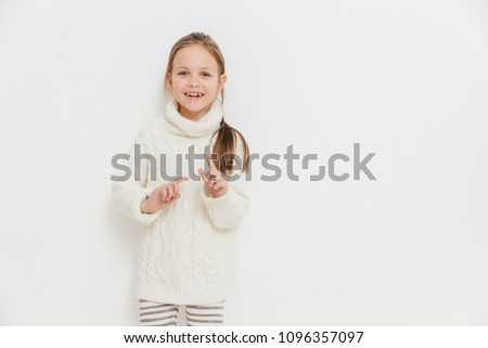 Attractive small female child in warm winter sweater, hears positive story from friend, stands again Stock photo © vkstudio