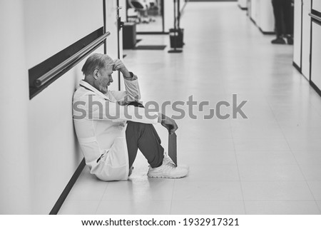 Side view of a depressed Caucasian male surgeons sitting with his head in his hands in the corridor  Stock photo © wavebreak_media