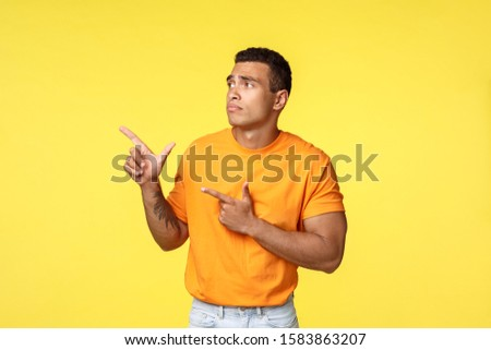 Jealous and upset gloomy cute masculine man, wear orange t-shirt, standing unhappy and sad over yell Stock photo © benzoix