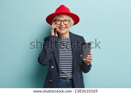 Horizontal shot of happy woman has telephone conversation, has spare time, sits at green bag, poses  Stock photo © vkstudio