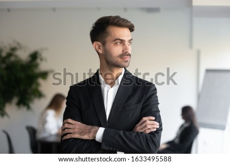 Self assured male CEO in formal suit stands crossed hands, looks with satisfied expression into dist Stock photo © vkstudio