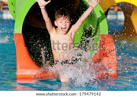 Happy boy on water slide in a swimming pool having fun during summer vacation in a beautiful tropica Stock photo © galitskaya