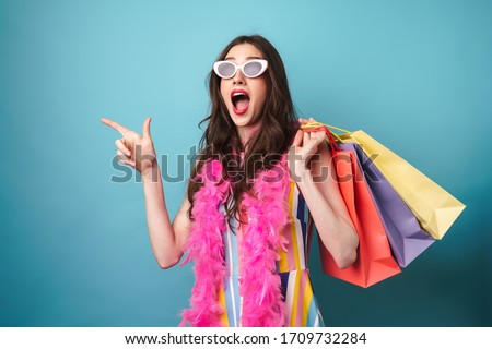 Photo of nice excited woman holding and pointing finger at passport Stock photo © deandrobot