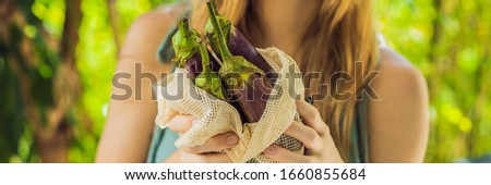 Eggplant in a reusable bag in the hands of a young woman. Zero waste concept Stock photo © galitskaya