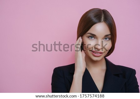 Photo of lovely European female entrepreneur with healthy skin, touches face gently, returns from sp Stock photo © vkstudio