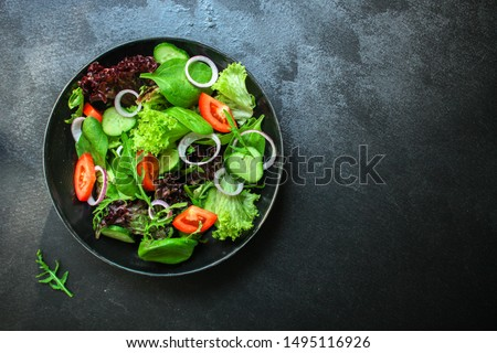 Cucumbers and tomatoes, red onion and spinach mix in fresh vegetables salad in grey bowl plate on da Stock photo © DenisMArt