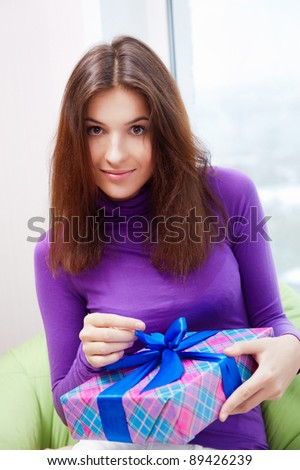 Delighted woman opening a gift sitting on the bean bag at home a Stock photo © HASLOO