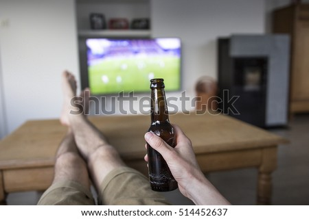 young man holding soccer ball and beer and watching tv translati stock photo © hasloo