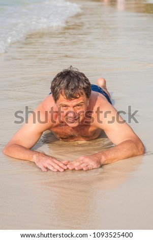 Man in bathingsuit is lying at the beach and enjoying the saltwa Stock photo © meinzahn