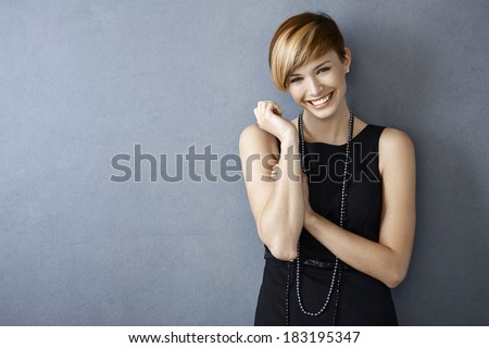 Young beautiful woman in black dress standing on gray background Stock photo © deandrobot