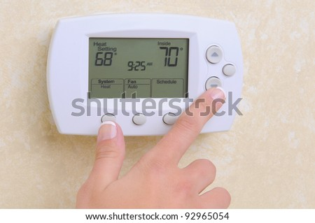closeup of a womans hand setting the room temperature on a mode stock photo © bubutu