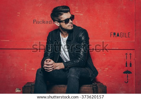 male sitting on a box in wooden studio background while touching stock photo © feedough