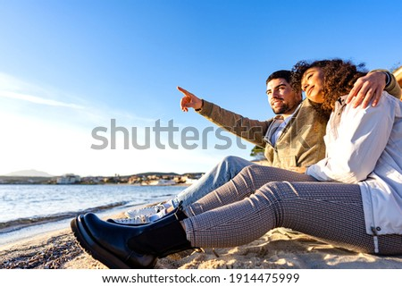 Man and girl sitting on seashore. With smile in looking at laptop standing on their knees. Vertical  Stock photo © Paha_L
