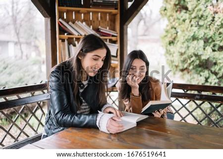 Derűs nővérek ikrek olvas könyv nevet Stock fotó © deandrobot