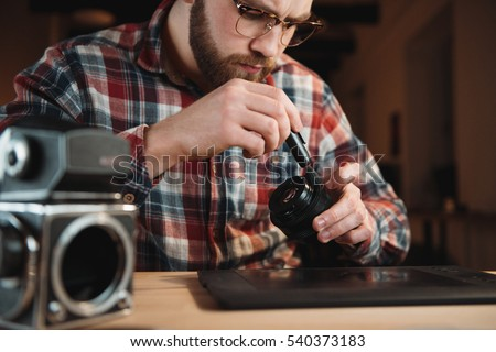 Young engineer fixing vintage camera while sitting at his workplace Stock photo © deandrobot