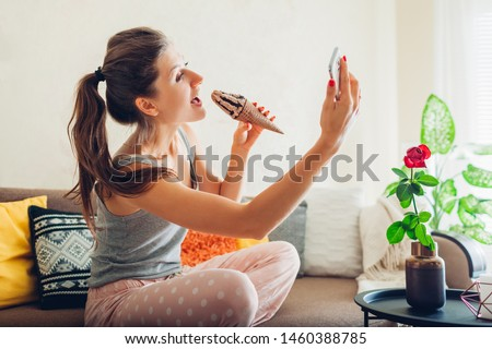 Cheerful young woman eating dessert and taking selfie in cafe Stock photo © deandrobot