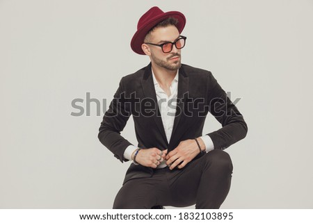fashion man wearing rings and sunglasses unbuttoning his coat  Stock photo © feedough