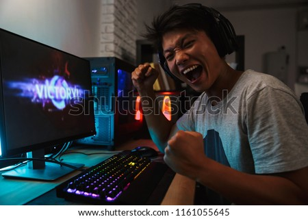 Cheerful asian gamer boy rejoicing victory while playing video g Stock photo © deandrobot