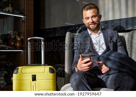 Przystojny biznesmen teczki posiedzenia czeka Zdjęcia stock © feedough