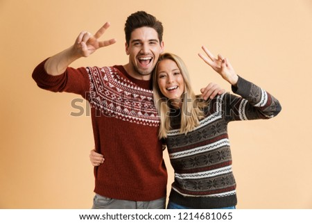 loving couple in sweaters hugging isolated over beige background showing peace gesture stock photo © deandrobot