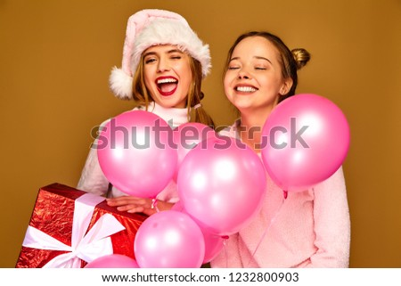 Image of two caucasian girls smiling and posing with gift box, i Stock photo © deandrobot