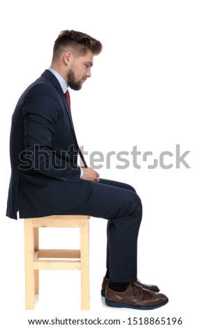 attractive businessman in navy suit sitting and arranging his bo Stock photo © feedough