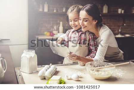 beautiful mother and her cute little daughter are using a tablet at home stock photo © lopolo