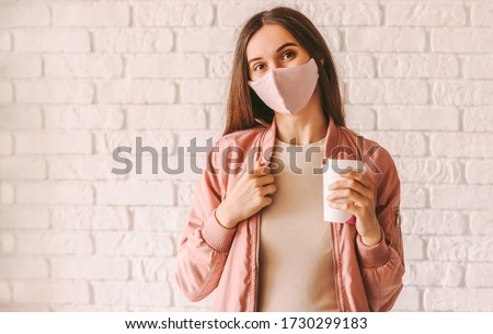 Image of beautiful woman wearing jacket holding takeaway coffee  Stock photo © deandrobot