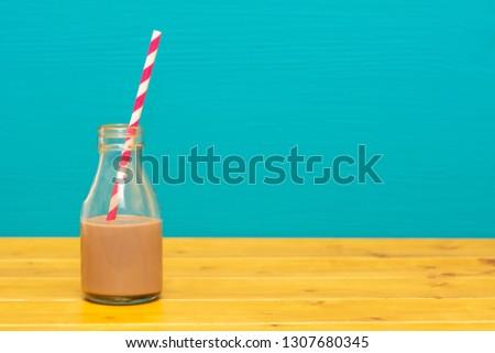 Glass bottle half full with chocolate milkshake with paper straw Stock photo © sarahdoow
