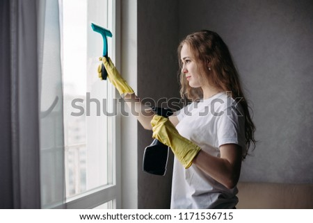 Side view of curly girl wearing protective gloves cleaning window. Stock photo © studiolucky