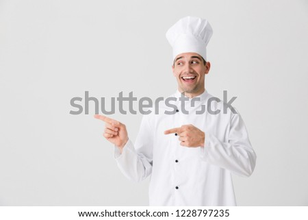Excited young man chef indoors isolated over white wall background holding frying pan cooking meat. Stock photo © deandrobot