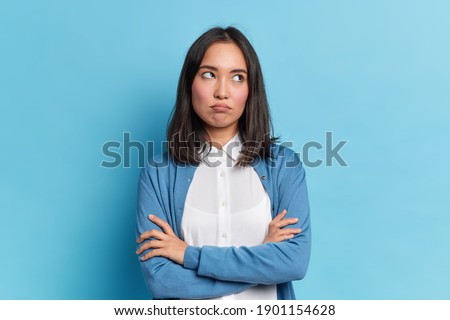 Displeased young asian beautiful woman isolated over blue background covering ears. Stock photo © deandrobot