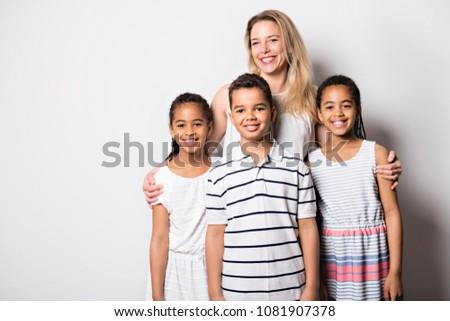 caucassian mother with black twin and son child in studio white Stock photo © Lopolo