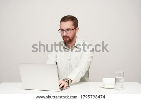 Image of concentrated unshaved businessman 30s in white shirt ho Stock photo © deandrobot